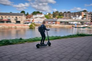 Riding an Ampere Go Electric Scooter next to a canal