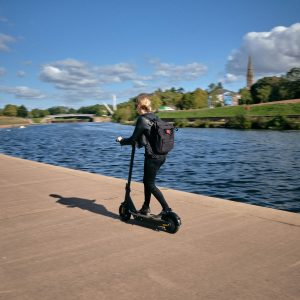 Riding an Ampere Go Electric Scooter next to the water